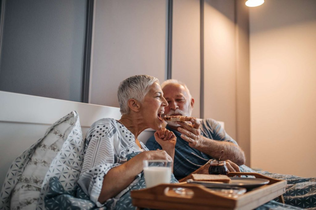 An elderly couple eating breakfast in bed