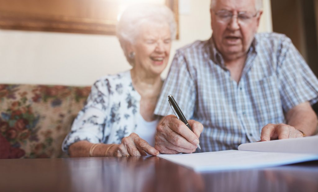 An elderly couple laughing signing documents